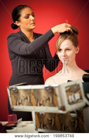 stylist making up a young woman wearing a bride's dress