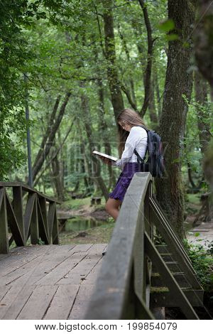 Pretty Little Blonde Schoolgirl With Backpack Standing On A Bridge In The Nature And Reading A Book