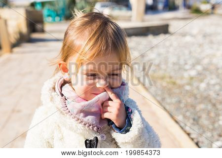 Cute little toddler baby girl picking her nose.