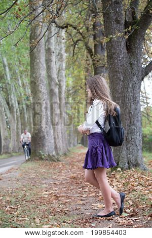 Pretty Little Long Hair Blonde Schoolgirl With Backpack Posing And Standing In The Alley Park Holdin