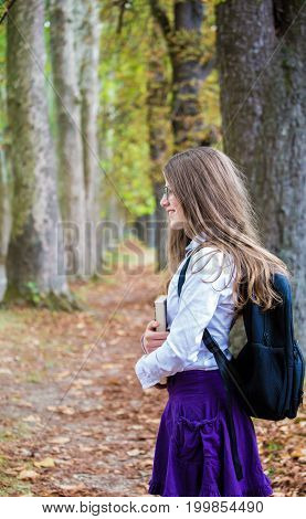 Pretty Little Blonde Schoolgirl With Backpack And Long Hair Standing In The Alley Park Holding Books