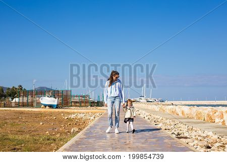 mother and daughter walking holding their hands