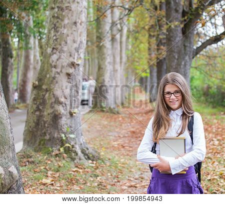 Pretty Beautiful Blonde Child Schoolgirl Back To School Standing And Smiling In Tree Alley In Autumn