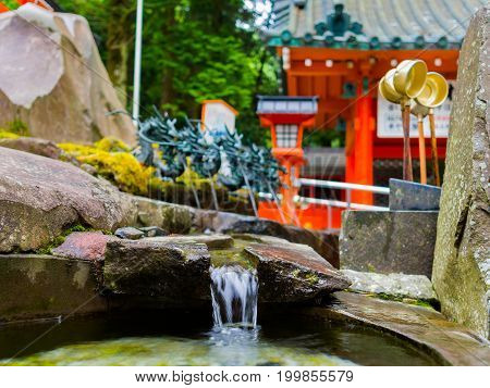 HAKONE, JAPAN - JULY 02, 2017: Close up of a pond with a blurred red Tori Gate behind, at Fushimi Inari Shrine in Kyoto, Japan.