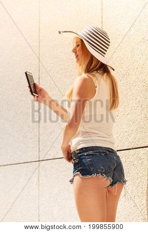 Technology internet social media concept. Young woman wearing sun hat using her smartphone. Outdoor shot on sunny summer day