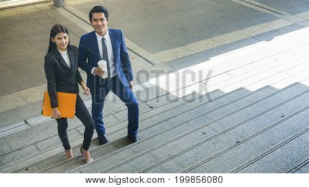 the smart business people of man and woman walk together in feeling happy at the outdoor pedestrian walkway space in the morning.