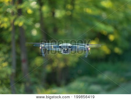 MOLDOVA CHISINAU - AUGUST 11 2017: DJI Mavic Pro drone flying for video shooting on the green park at the summer day