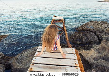 Young happy woman sitting on wooden pier and laughing
