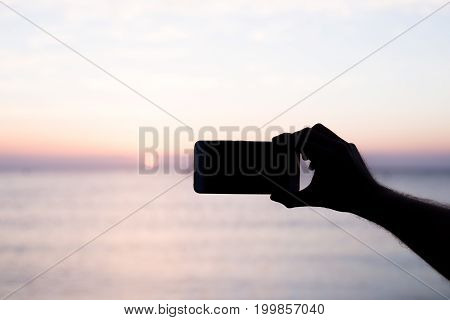 silhouette hand holding smartphone take photo at sunset