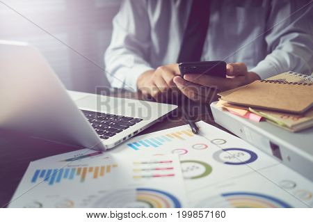 businessman hand working smart phone on wooden desk in office in morning light. The concept of modern work with advanced technology. vintage effect
