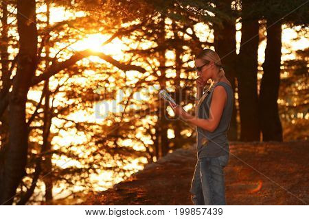 Traveler woman in the forest enjoying sunset, pretty girl standing in the woods with map in hand and searching right direction, active summer adventure