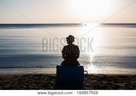 Man silhouette sitting alone with suitcase on stony beach and watching romantic colorful sunrise