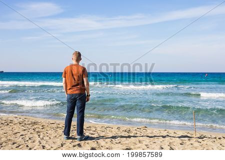 handsome man standing on the sandy beach.