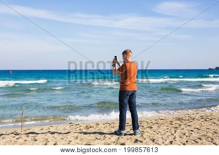 man taking photos of sea with mobile phone