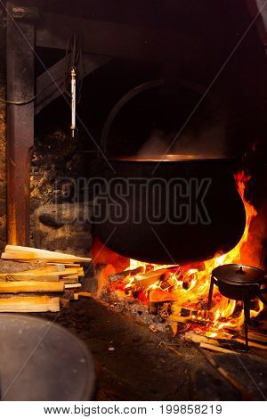 traditional cheesemaking - a huge pot of milk is heating up over a big wood fire.