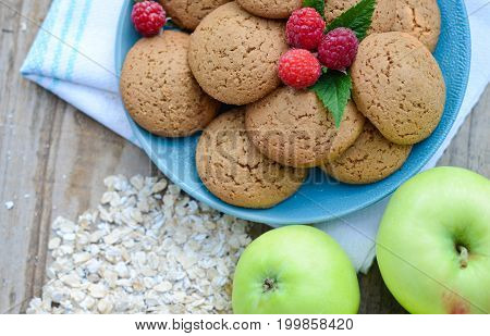 Oatmeal cookies with berry raspberries in a Cup of the green apples next to a bunch of flakes oatmeal ha wooden Board
