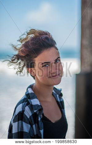 Happy teen head shot at beach with female looking to right with amused look.