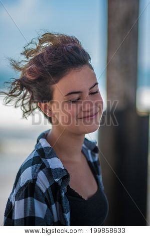 Happy teen head shot at beach with female looking down with amused look.