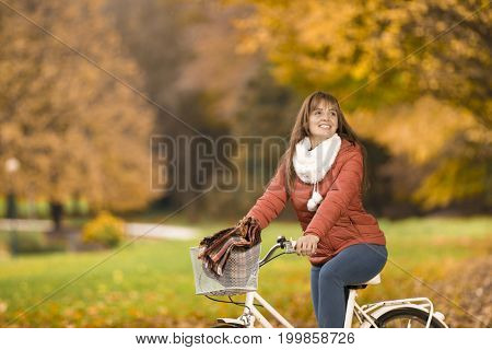 Smiling woman standing with bike in Autumn park