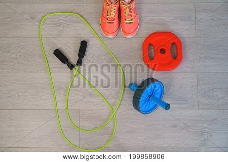 Flat lay of fitness and workout accessories, red dumbbells, water bottle and sneakers on wood background