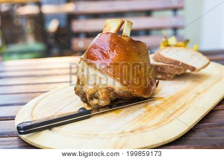 Roasted knuckle of pork on wooden board.