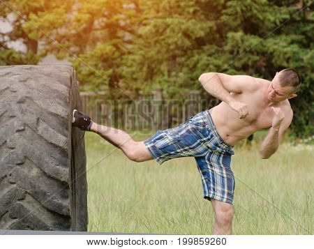 Young Man Is Kicked A Foot  In A Tire. Workout