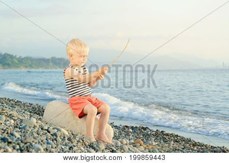 Boy In A Striped T-shirt Is Sitting On The Beach With A Wand. Sea In The Background