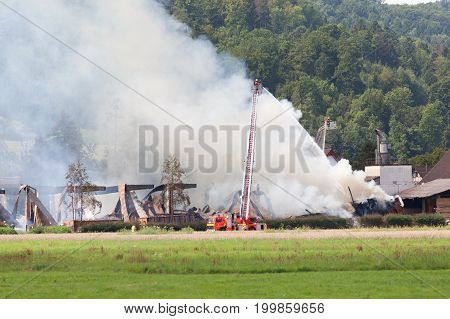 fireman extinguish fire bg burn with destroyed building