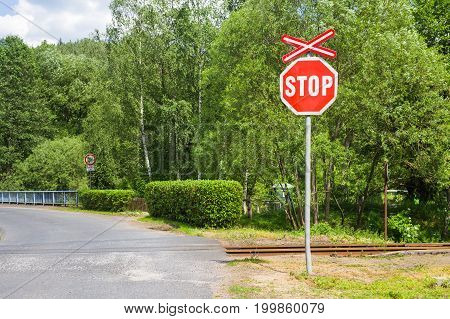 Stop and Railway crossing signs over blue sky background.