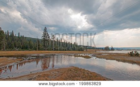 Tangled Creek Emptying Into Hot Lake Hot Spring Under Cumulus Clouds In The Lower Geyser Basin In Ye
