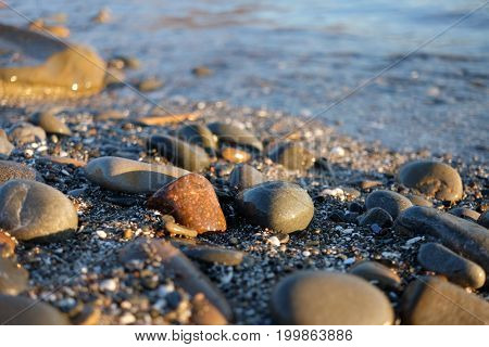 Pebble stones near the sea in bright sunset light background