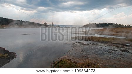 Tangled Creek emptying into Hot Lake hot spring under  clouds in the Lower Geyser Basin in Yellowstone National Park in Wyoming United States