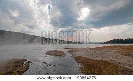 Tangled Creek flowing into Hot Lake hot spring under cumulus clouds in the Lower Geyser Basin in Yellowstone National Park in Wyoming United States