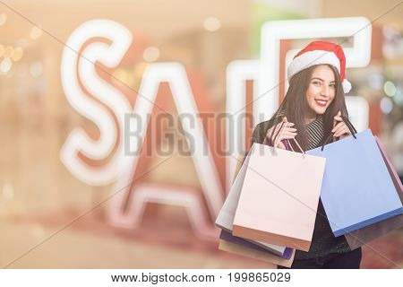 Beautiful young girl wearing a Santa hat holding lots of shopping bags in the festive season