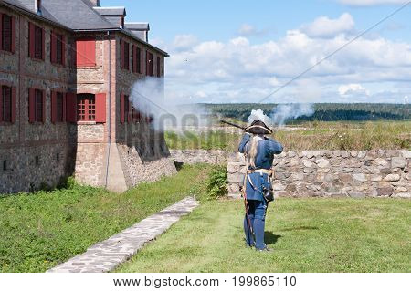 Re-enactment of a Soldier at the Fortress of Louisbourg firing his musket