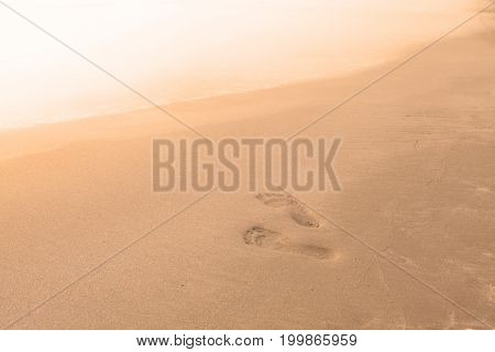 Blurry Background Of Beach And Sea Waves With Feet Stamp On Sand, Vintage Color Style.
