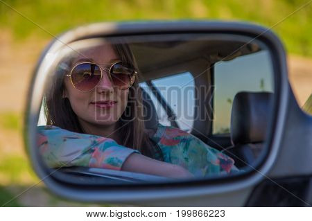Young Woman Driver In The Car Looking To The Side View Mirror