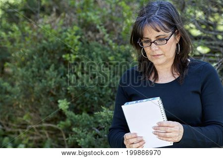Attractive middle aged woman wearing reading glasses looking down at notebook in her hands in an outdoor setting