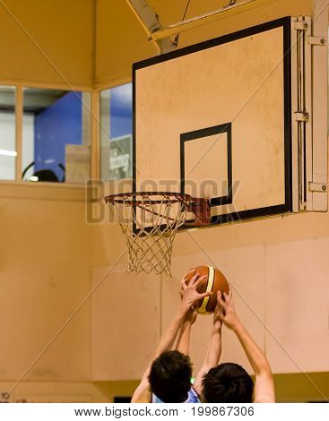 Two basketball players contesting the ball with a net and hoop in the background