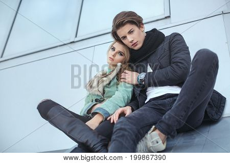 Fashion young couple in rock style hugging each other. Pretty girl and handsome man posing outdoors in city street