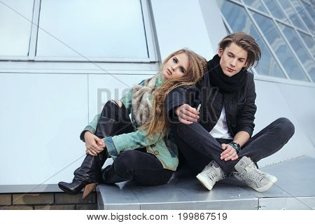 Teenage couple smoking. Fashion rock style. Pretty girl and handsome man sitting outdoors in city street