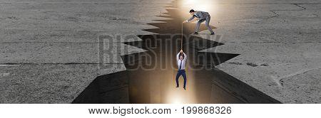 Man saving colleague pulling rope