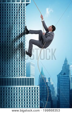 Businessman climbing skyscraper in challenge concept