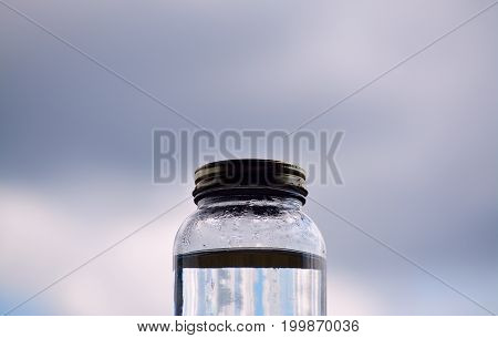 Jar of water against a stormy sky.