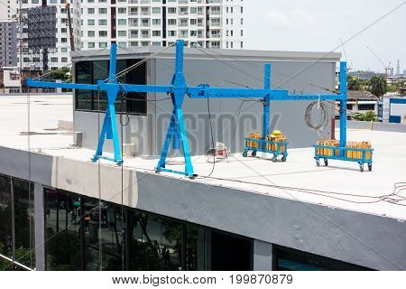 Lifting hoist operating on roofing top. Mobile hoist