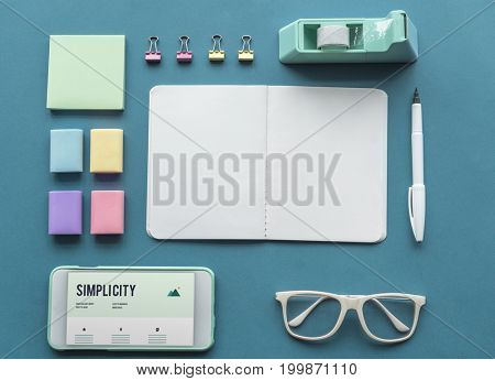 Simplicity word on smart-phone screen and office supplies