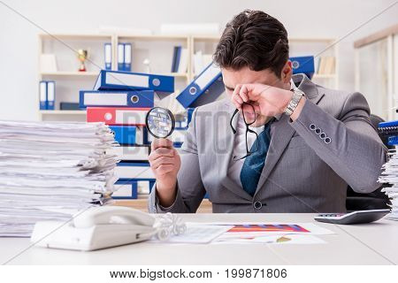 Male businessman with magnifying glass in office