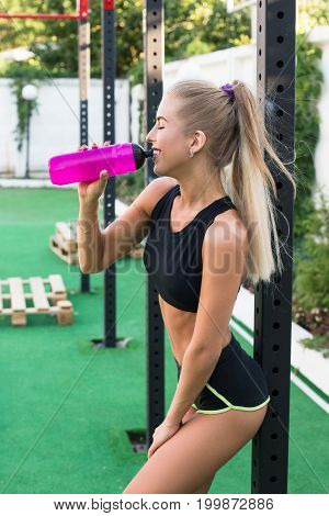 Lough and hot sport workout Attractive young woman in short shorts and top posing near playground and drink water. Sexy blond girl with bottle of water.Long blond hair of beautiful woman.