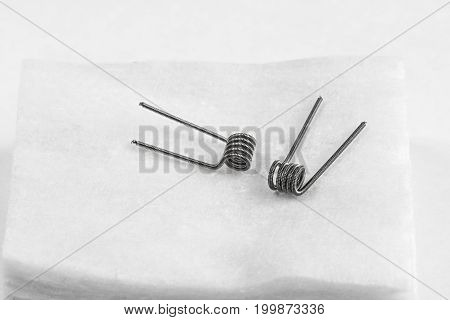 Two Clapton coils lying on the white cotton background isolated closeup