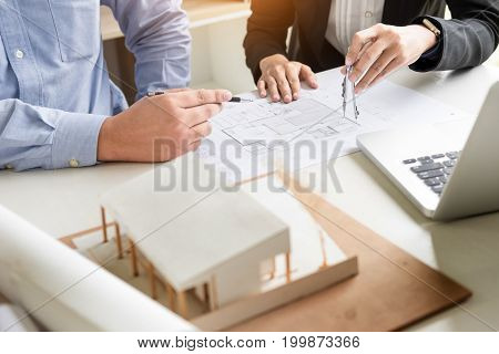 Person's engineer Hand Drawing Plan On Blue Print with architect equipment.